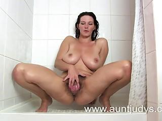 Грудастая девушка мастурбирует волосатую письку под душем в любительском порно