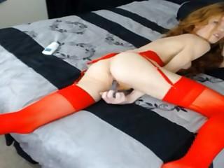 Рыжая бестия в красных чулках пихает в бритую пизду любимую секс игрушку